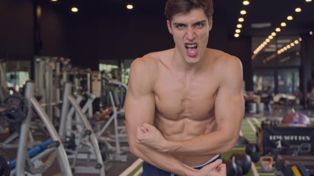 4k auflösung zeitlupe portrait junge stattliche mann zeigen starke bodybuilder zeigt seine muskulöse fit körper. männer gesunde lebensweise konzept - bodybuilding stock-videos und b-roll-filmmaterial