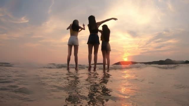 4k 解像度の夏の楽しいコンセプト、女性の友人のグループは、ビーチで一緒にジャンプ - 撮影点の映像素材/bロール