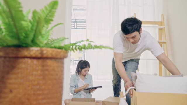 4k resolution young asian couple carrying boxes into new home on moving day.relocation concept - front door stock videos & royalty-free footage