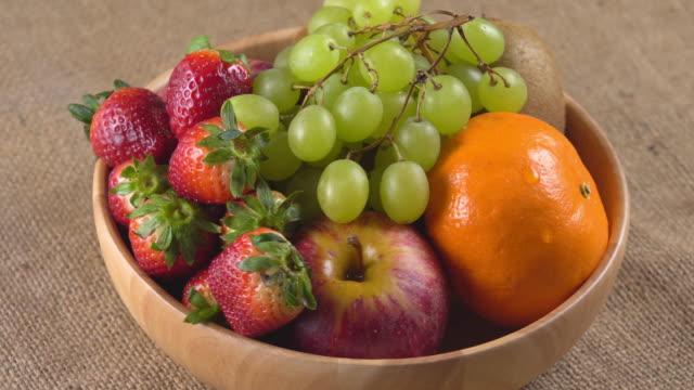 4k rotate of mix fruit in wooden bowl. - fruit bowl stock videos & royalty-free footage