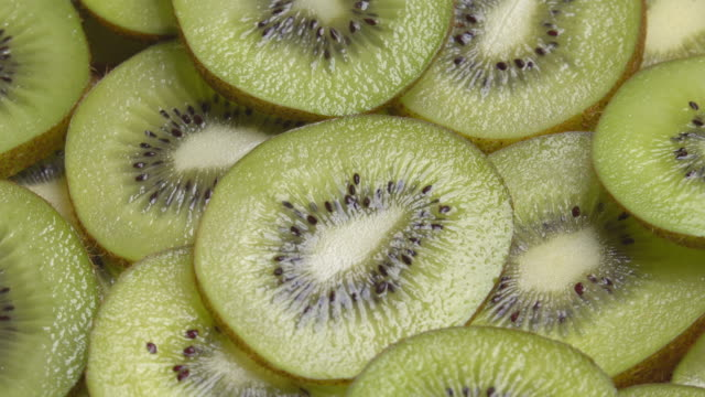 4k rotate of slice kiwi pattern. - kiwi fruit stock videos and b-roll footage