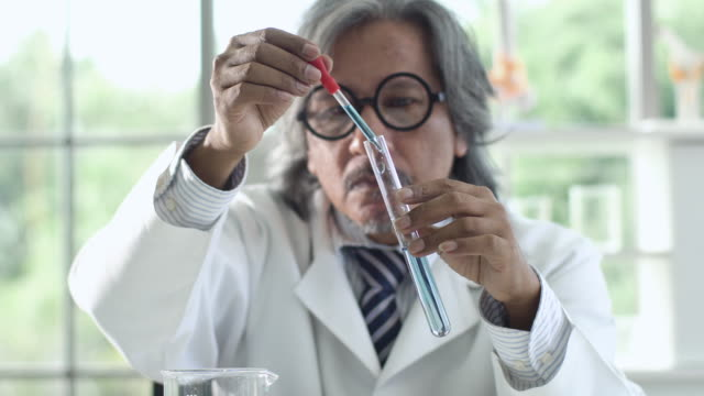 4k: scientist drop liquid in a test tube and shaking in laboratory. - professor stock videos & royalty-free footage