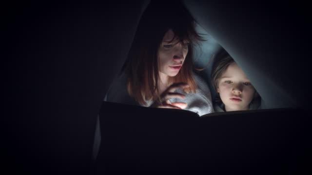 4k Shot of Child and Mom under Blanket Reading Horror Story Book