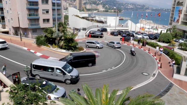 4k shot of famous hairpin curve corner in monte carlo, monaco part of the monaco forumla one grand prix. showing everyday cars, buses and occasional sports cars using the road. - トラック競技点の映像素材/bロール