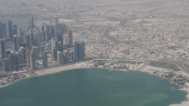 4k slow motion aerial view of doha qatar cityscape and skyline during flight. view of skyscrapers, business district and the downtown city area showing the built transport and infrastructure in the desert. - doha bildbanksvideor och videomaterial från bakom kulisserna