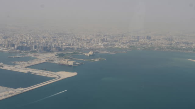 4k slow motion aerial view of doha qatar cityscape and skyline during flight. view of skyscrapers, business district and the downtown city area showing the built transport and infrastructure in the desert. - doha stock videos & royalty-free footage