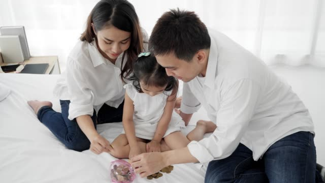 4k slow motion ,asian family depositing coins into piggy bank in white bed room. - soft focus stock videos & royalty-free footage