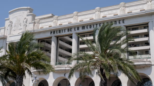 vídeos y material grabado en eventos de stock de 4k slow motion clip of casino du palais de la méditerranée in nice, france. showing the building and palm trees gently swaying in the breeze on a bright summer warm day. - francia