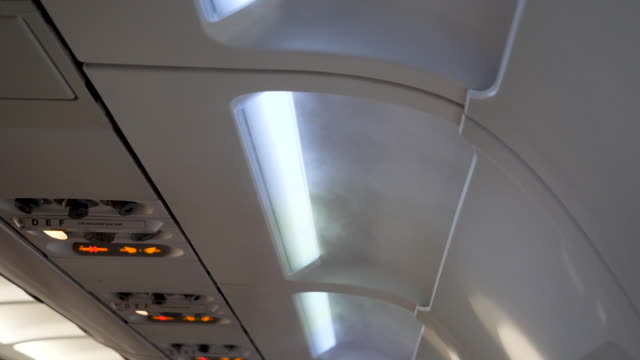4k slow motion close up of visible white coloured air or gas coming from the aeroplanes ventilation system during flight. likely over powered air conditioning - bremskeil stock-videos und b-roll-filmmaterial