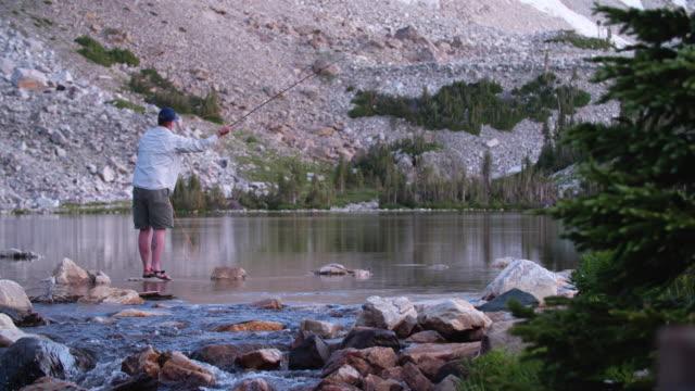 4k slow motion fly fishing inmountain lake at sunrise - fishing line stock videos & royalty-free footage
