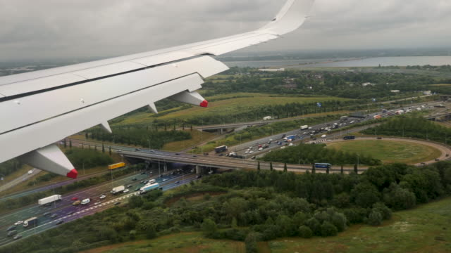 4k slow motion landing at london heathrow airport. aerial footage of rural english countryside showing motorways, green fields, farms and crops on a summers day. shot through window of aeroplane. - flughafen heathrow stock-videos und b-roll-filmmaterial
