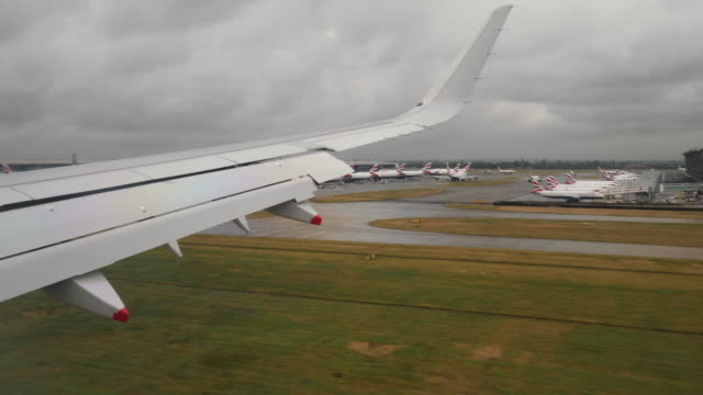 4k slow motion landing at london heathrow airport. aerial footage of rural english countryside showing motorways, green fields, farms and crops on a summers day. shot through window of aeroplane. - high up stock videos & royalty-free footage