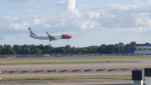 4k slow motion shot of norwegian air commercial passenger plane landing at london gatwick airport lgw. plane travelling from left to right in shot followed by emergency vehicle - commercial land vehicle stock videos & royalty-free footage