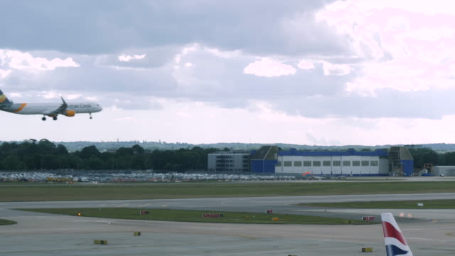 4k slow motion shot of thomas cook commercial passenger plane landing at london gatwick airport lgw. plane travelling from left to right in fixed shot. - airplane hangar stock videos & royalty-free footage