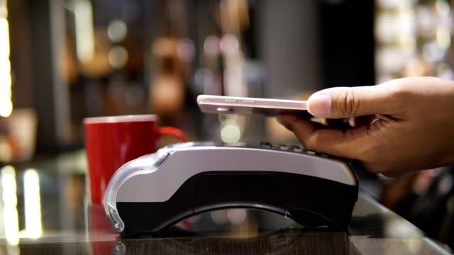 4kスローモーション、コーヒーショップの顧客は、モバイルアプリケーション、電子商取引のマネーレスコンセプトでお金を支払います。 - クレジット決済点の映像素材/bロール