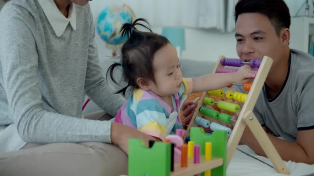 4k slowmotion,asian family playing wooden multi color toy with baby girl.education for baby concept. - genius stock videos & royalty-free footage