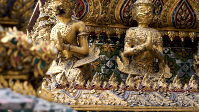 4k smooth panning close up of golden statues in the grand palace bangkok thailand. - 王宮点の映像素材/bロール