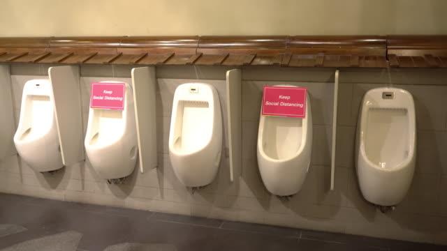 4k コロナウイルス病の感染を避けるために洗面所の小便器の社会的距離 - 小便器点の映像素材/bロール