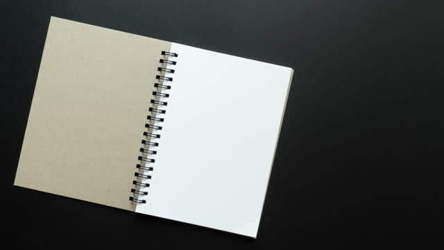 4k stop motion of  notebook open with blank page on black background - note pad stock videos & royalty-free footage
