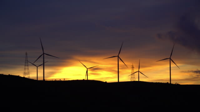 4k Sunset of Farm of Wind Turbine for Alternative Energy.