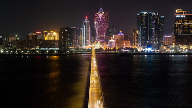 4k time lapse: aerial panorama view of car light trails run toward illuminated hotel buildings in macao city. tilt down shot - macao stock videos & royalty-free footage
