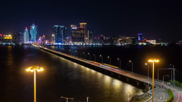 4k time lapse: aerial view of traffic car light trails on the bridge run toward illuminated hotel buildings at night, macao. - macao stock videos & royalty-free footage
