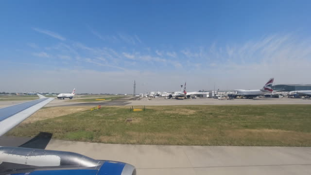 4k time lapse from aeroplane window during taxi to runway at london heathrow airport, united kingdom. showing terminal 5 and many other planes taxiing to the runway waiting to take off on a bright summer warm day. - clear sky stock videos & royalty-free footage