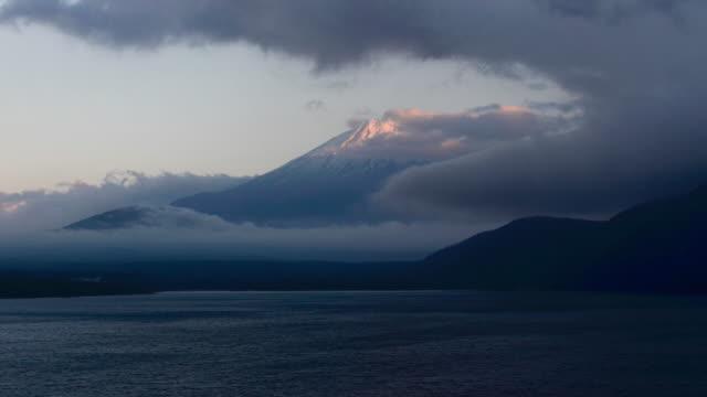 vídeos de stock, filmes e b-roll de 4 k tempo lapso montanha fuji com pôr do sol e nuvem de noite no lago motosu, prefeitura de yamanashi, região de chubu, japão - vídeo de estoque - desaparecer gradualmente