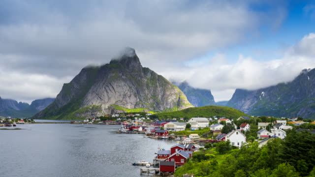 4k time lapse moving clouds over traditional norwegian fisherman's cabins, rorbuer, on the island of hamnoy, reine, lofoten islands, summer of norway. - village stock videos & royalty-free footage