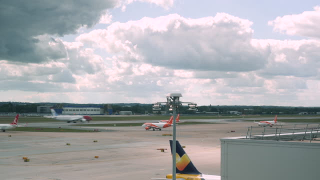 4k time lapse of london gatwick airport lgw runway showing aeroplanes taxiing queuing for take off and landing at busy congested airport. shows a variety of small, medium and large planes. - finance and economy stock videos & royalty-free footage