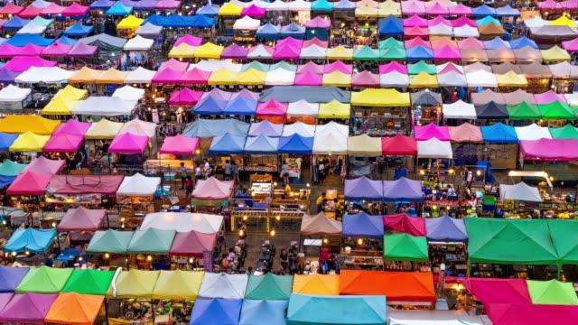 4k time lapse von menschen, die auf dem nachtmarkt in bangkok thailand zum abend spazieren gehen, schließen sie die thailändische sprache in den clip ein, es bedeutet den namen jedes ladens - einkaufstasche stock-videos und b-roll-filmmaterial