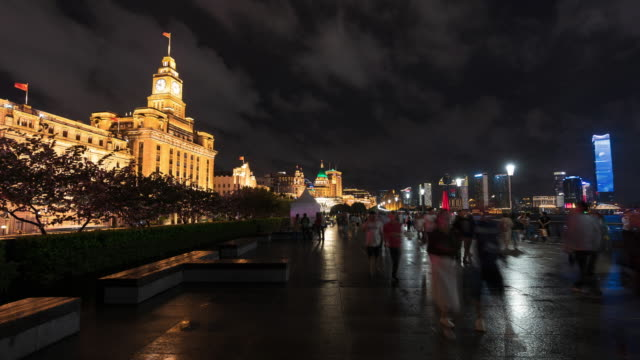 4k time lapse: people walking along the sightseeing viewpoint at the bund at night with illuminated buildings, shanghai, china - the bund stock videos & royalty-free footage