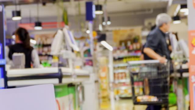 vidéos et rushes de laps de temps 4 k l'argent de paiement foule au supermarché - queue