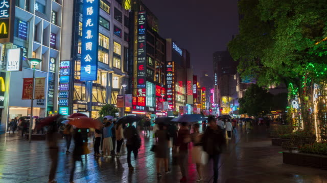 4k time lapse: tourist pedestrian crowd walking at nanjing road shopping street at night with reflection, shanghai city, china. - nanjing stock videos & royalty-free footage