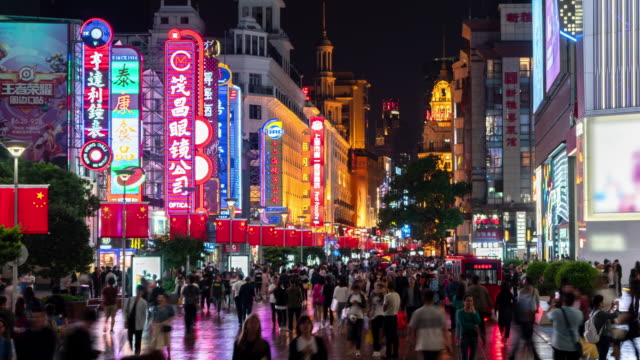 4k time lapse: tourist pedestrian crowd walking at nanjing road shopping street which decorated with chinese flag, shanghai city, china. - nanjing stock videos & royalty-free footage