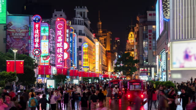 4k time lapse: tourist pedestrian crowd walking at nanjing road shopping street which decorated with chinese flag, shanghai city, china. - chinese flag stock videos & royalty-free footage