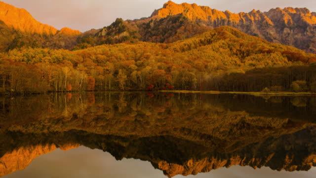 4k time lapse wide shot of kagamiike pond in autumn season, nagano, japan. - high dynamic range imaging stock videos and b-roll footage