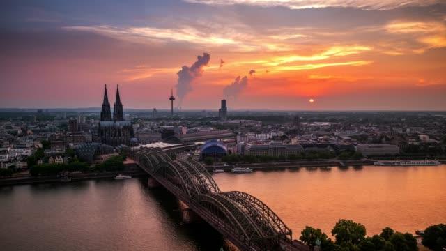 4k timelapse: kölner dom hohenzollernbrücke bei sonnenuntergang, deutschland - hauptverkehrszeit stock-videos und b-roll-filmmaterial
