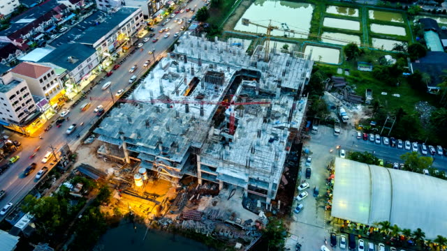4k time-lapse: aerial view of working construction site - realizzazione video stock e b–roll