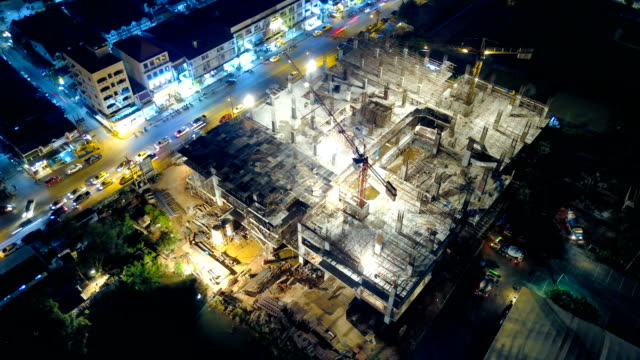4k time-lapse: aerial view of working construction site - skyscraper stock videos & royalty-free footage