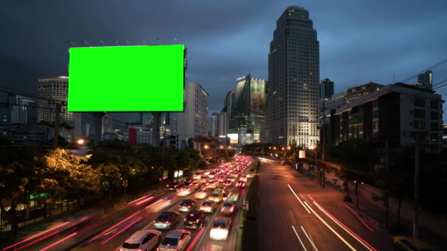 4k timelapse day to night of light trails in road to asoke district at the center of heart business district in bangkok city downtown thailand - tabellone video stock e b–roll