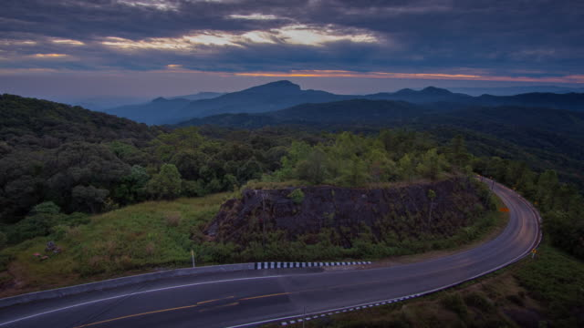 4k time-lapse lockdown of winding road on mountain pass at sunrise.