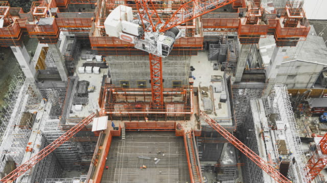 4k timelapse of  aerial view of working construction site large construction site including several cranes working on a building area zoom view - architecture stock videos & royalty-free footage