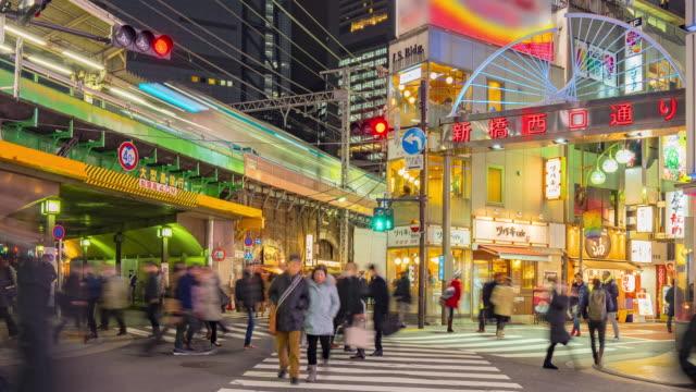4k time-lapse van Shimbashi commerciële en nacht leven wijk vlakbij shimbashi station met de menigte van mensen (inzoomen camera)