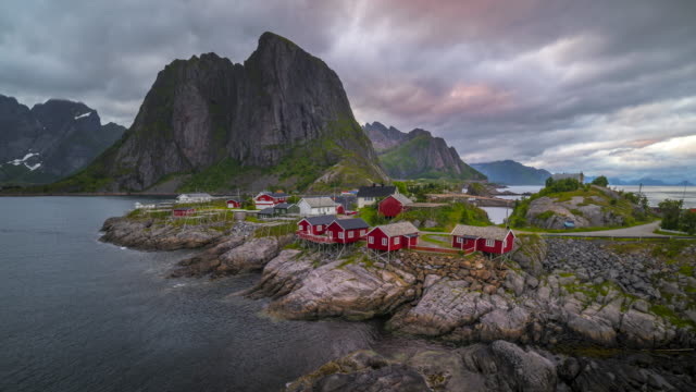 4k timelaspe moving clouds over traditional norwegian fisherman's cabins, rorbuer, on the island of hamnoy, reine, lofoten islands, summer of norway. - village stock videos & royalty-free footage