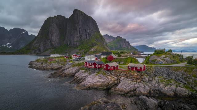 stockvideo's en b-roll-footage met 4 k timelaspe bewegende wolken boven traditionele noorse vissersstrand hutten, rorbuer, op het eiland van hamnoy, de reine, lofoten eilanden, noorwegen zomer. - village
