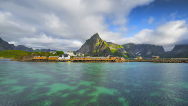 vídeos de stock e filmes b-roll de 4k timelaspe moving clouds over traditional norwegian fisherman's cabins, rorbuer, on the island of hamnoy, reine, lofoten islands, summer of norway. - norte