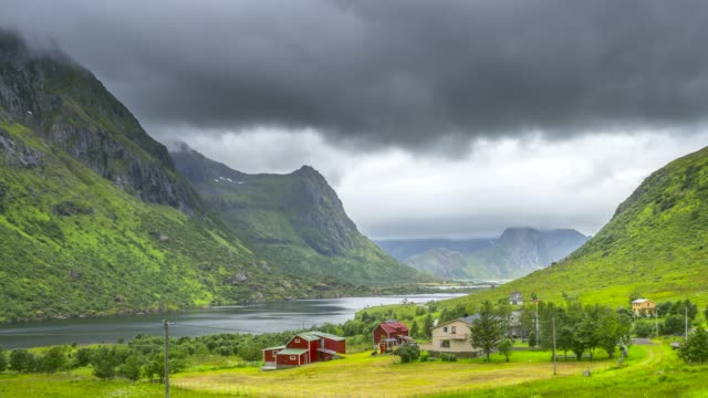 4k timelaspe moving clouds over traditional norwegian fisherman's cabins, rorbuer, on the island of hamnoy, reine, lofoten islands, summer of norway. - season stock videos & royalty-free footage