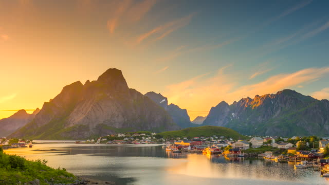 4k timelaspe panning of  moving clouds over traditional norwegian fisherman's cabins, rorbuer, on the island of hamnoy, reine, lofoten islands, summer of norway. - norvegia video stock e b–roll