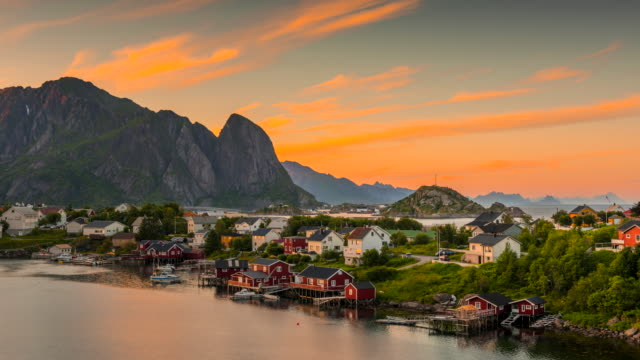 4k timelaspe Sunset Scene of Moving clouds over traditional Norwegian fisherman's cabins, rorbuer, on the island of Hamnoy, Reine, Lofoten islands, Summer of Norway.